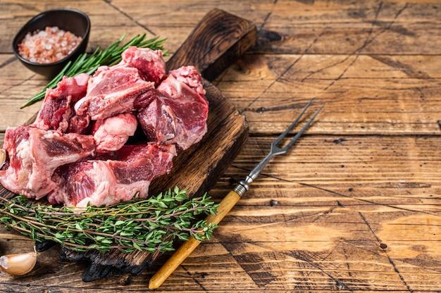 Surowe mięso wołowe pokrojone w kostkę na gulasz z kością. drewniane tła. widok z góry. skopiuj miejsce.