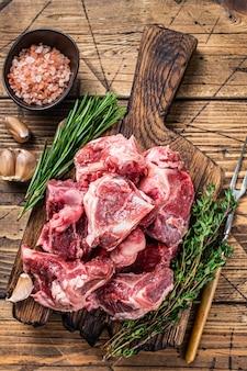Surowe mięso wołowe pokrojone w kostkę na gulasz z kością. drewniane tła. widok z góry.