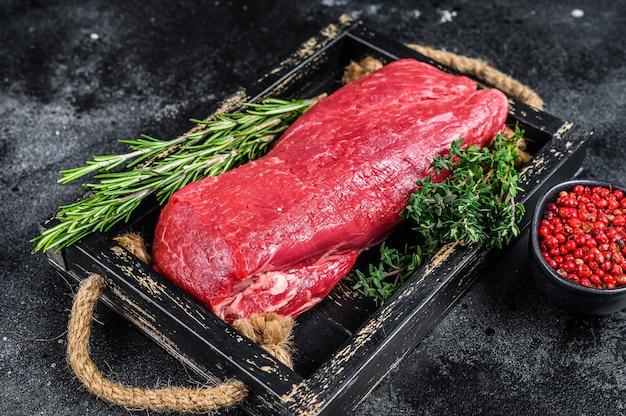 Surowe mięso wołowe w całości polędwicy na drewnianej tacy z ziołami. czarne tło. widok z góry.