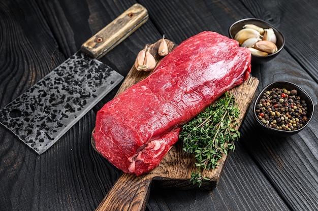 Surowe mięso wołowe z polędwicy na steki filet mignon na drewnianej desce do krojenia