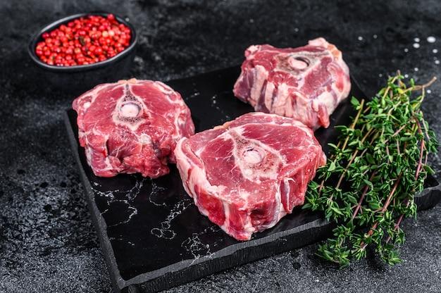Surowe mięso z karkówki jagnięcej na marmurowej desce. czarne tło. widok z góry.