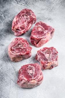 Surowe mięso z karkówki jagnięcej na stole do gotowania. białe tło. widok z góry.