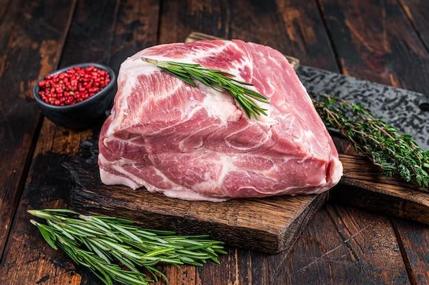 Surowe mięso z karkówki na świeże steki pokroić na drewnianą deskę do krojenia z tasakiem rzeźniczym. ciemne drewniane tło. widok z góry.