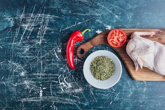 Surowe mięso z kurczaka na drewnianej desce.