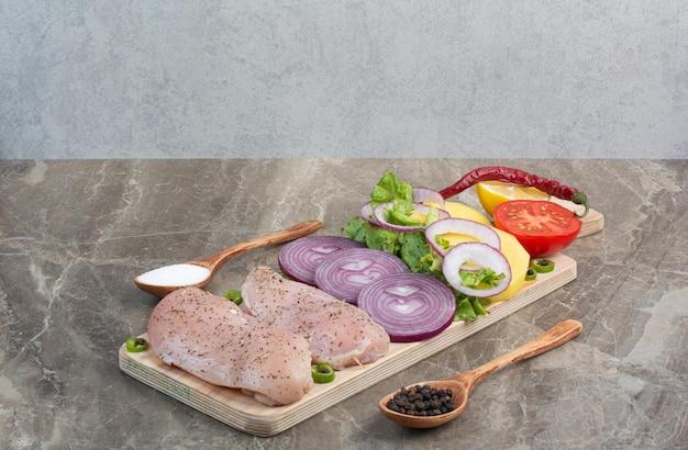 Surowe mięso z kurczaka z plastrami cebuli na desce. zdjęcie wysokiej jakości