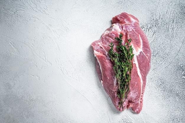 Surowe mięso z łopatki wieprzowej na stole rzeźnika. białe tło. widok z góry. skopiuj miejsce.
