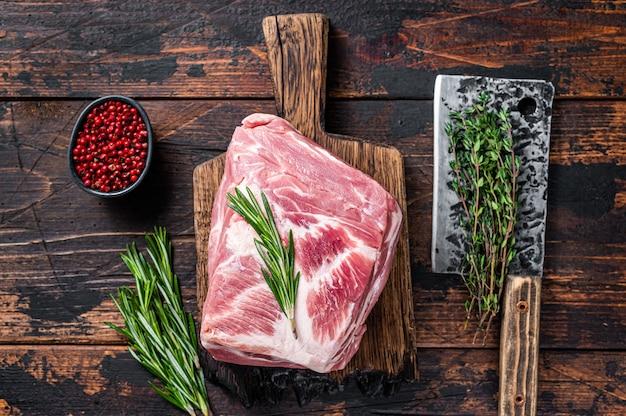 Surowe mięso z łopatki wieprzowej na świeże steki na drewnianej desce do krojenia z tasakiem rzeźniczym. ciemne drewniane tło. widok z góry.