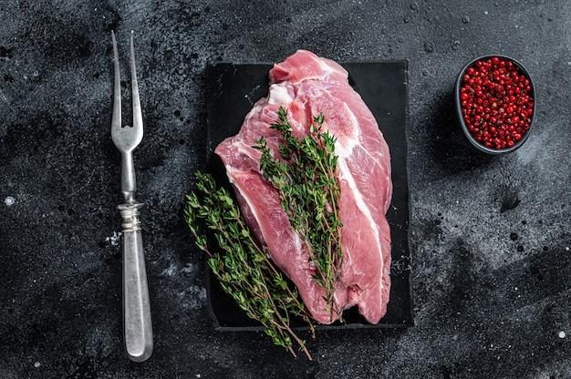 Surowe mięso z łopatki wieprzowej pokrojone na marmurowej desce. czarne tło. widok z góry.