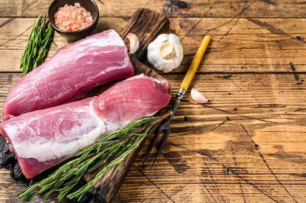 Surowe mięso z polędwicy wieprzowej. drewniane tła. widok z góry. skopiuj miejsce.