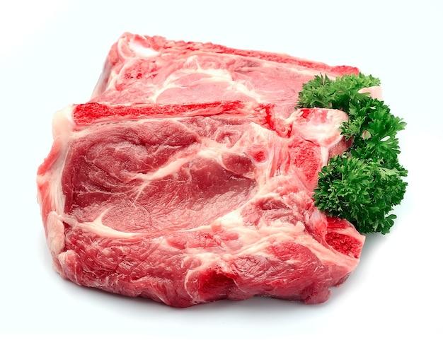 Surowe mięso z przyprawami na białym tle.
