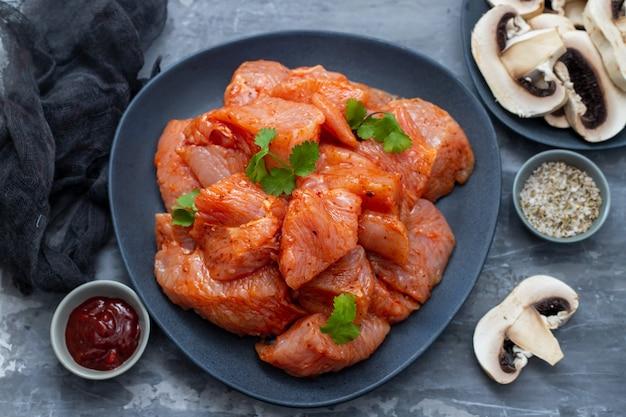 Surowe mięso z przyprawami na ciemnym naczyniu