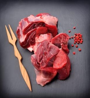 Surowe mięso z przyprawami na czarnym tle.