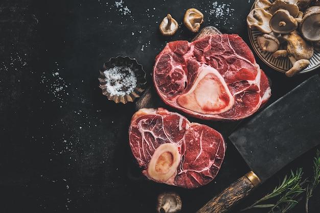 Surowe mięso z warzywami i przyprawami na ciemnym tle vintage. widok z góry.