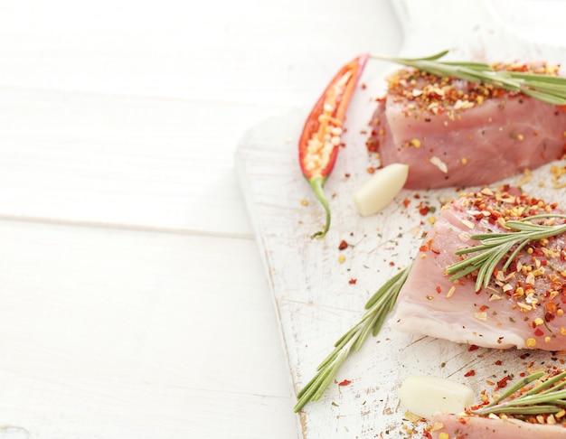Surowe mięso z ziołami i przyprawami na białej tablicy