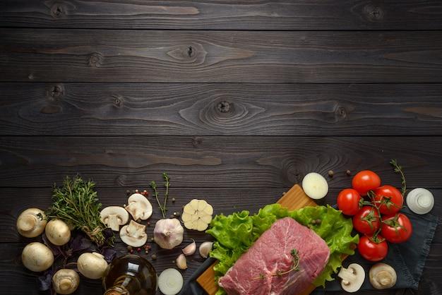 Surowe mięso ze składnikami na drewnianym stole