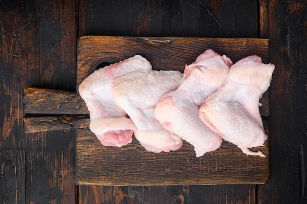 Surowe mięso. zestaw skrzydełek z kurczaka, na drewnianej desce do krojenia, na starym ciemnym drewnianym stole, widok z góry na płasko
