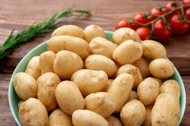 Surowe młode małe ziemniaki na drewnianym tle.