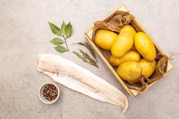 Surowe młode ziemniaki i mrożone filety z morszczuka z ziołami i przyprawami