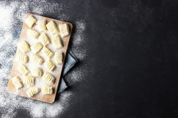 Surowe niegotowane domowe kluski ziemniaczane z mąką na desce do krojenia. widok z góry. ciemne tło.