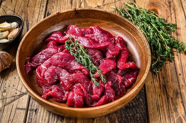 Surowe niegotowane mięso wołowe pokrojone w paski ze świeżymi ziołami na stroganow wołowy
