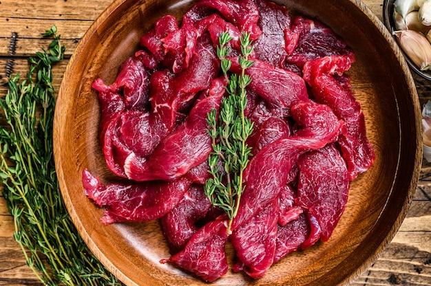 Surowe, niegotowane mięso wołowe pokrojone w paski ze świeżymi ziołami na stroganow wołowy.