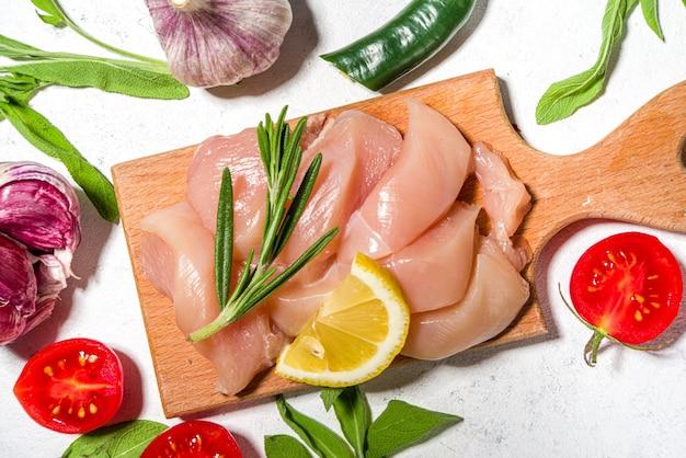 Surowe niegotowane paski mięsa z kurczaka, pokrojony w kostkę świeży surowy filet z piersi na desce do gotowania biały stół widok z góry