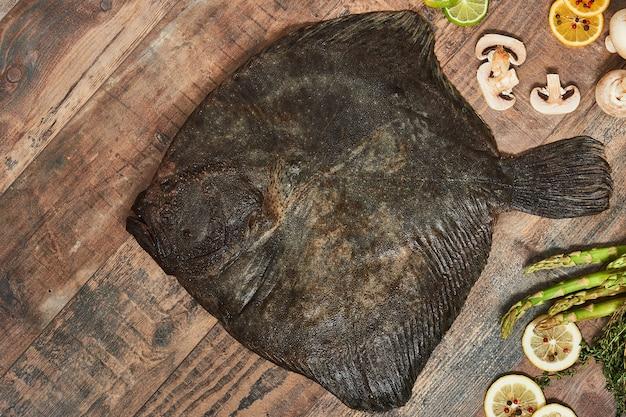 Surowe niegotowane płastugi z cytrynami, szparagami, ziołami, grzybami i przyprawami na drewnianym stole. gładzica europejska, widok z góry