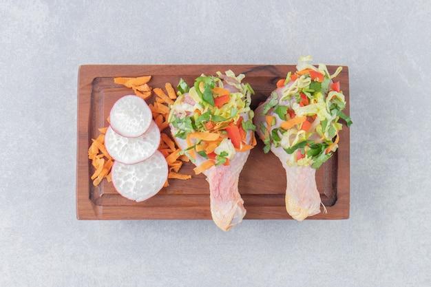 Surowe niegotowane udka z kurczaka, mięso z dodatkami do gotowania, na białej tablicy