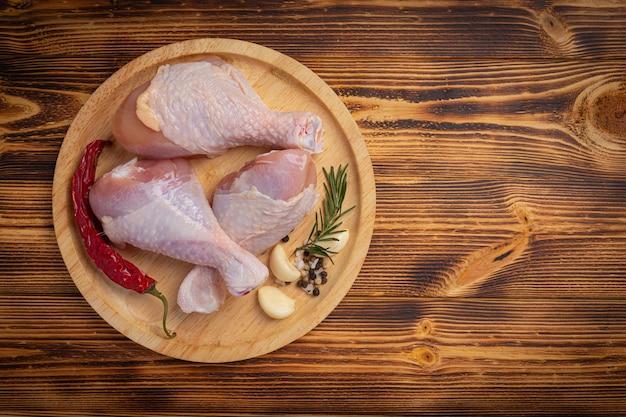 Surowe, niegotowane udka z kurczaka na ciemnej drewnianej powierzchni.