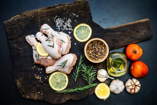 Surowe niegotowane udka z kurczaka na desce do krojenia, mięso z solą pieprzową i ziołami