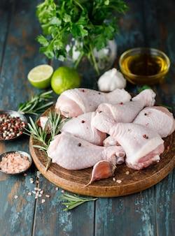 Surowe, niegotowane udka z kurczaka z przyprawami i składnikami do gotowania na desce do krojenia