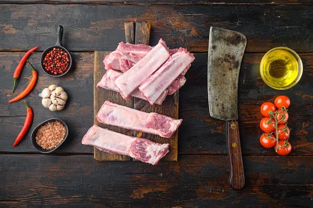 Surowe niegotowane żeberka wieprzowe, świeże mięso z zestawem składników, z miodem, ze starym nożem rzeźniczym, na starym ciemnym drewnianym stole, płaski widok z góry