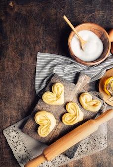 Surowe, niewypieczone, domowe słodkie bułeczki z miodem i cukrem na rustykalnej sklejce.