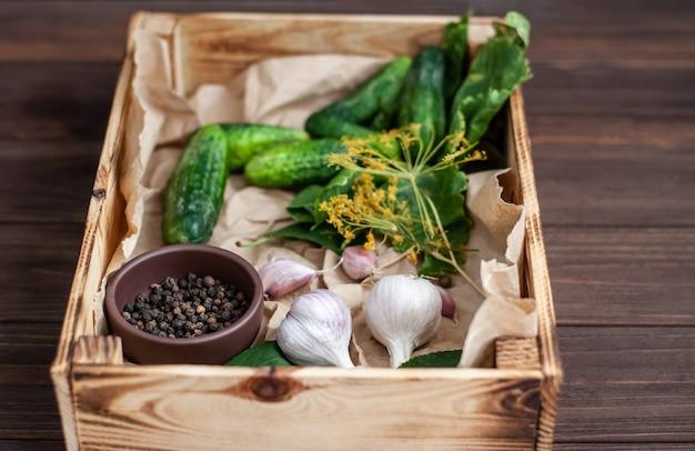Surowe ogórki, kwiaty koperku, liść wiśni, liść chrzanu, przyprawy i zioła na tacy na drewnianym stole.