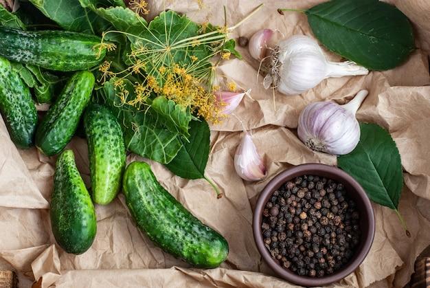 Surowe ogórki, kwiaty koperku, liść wiśni, liść chrzanu, przyprawy i zioła