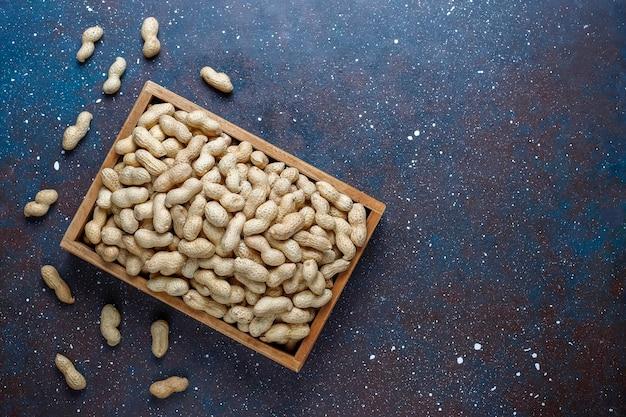 Surowe organiczne orzeszki ziemne w łupinach.