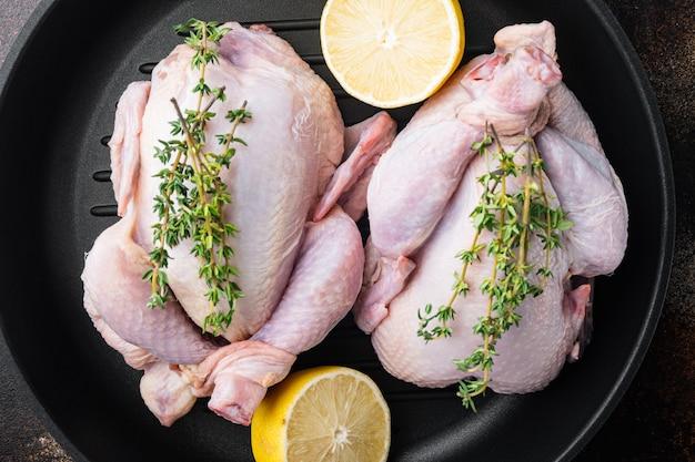 Surowe organiczne surowe mięso z całego kurczaka na patelni grillowej, na starym rustykalnym tle, widok z góry