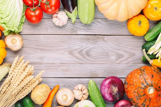 Surowe organiczne świeże warzywa na drewnianym stole. świeże jedzenie wegetariańskie w ogrodzie. jesień sezonowy obraz rolnika stół z pieczarkami, żyto, ogórki, dynie, cebula, pomidory i inne. wolna przestrzeń.