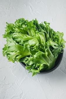 Surowe organiczne zielone liście sałaty dębowej, na białym tle