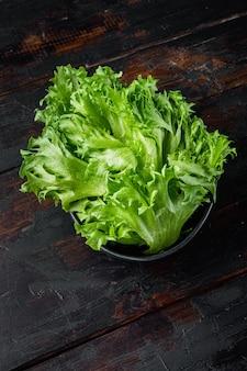 Surowe organiczne zielone liście sałaty dębowej, na starym ciemnym drewnianym stole