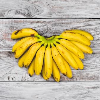 Surowe organiczne żółte banany dla dzieci w pęczku na białej powierzchni drewnianej widok z góry