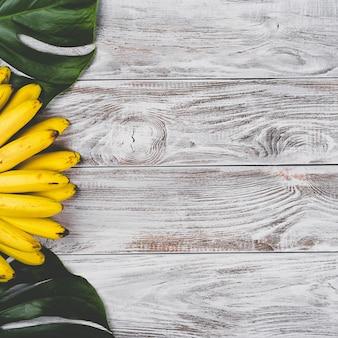 Surowe organiczne żółte banany dla dzieci w pęczku na białym drewnianym stole, widok z góry.