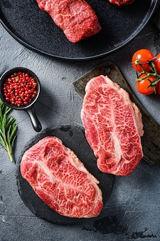 Surowe ostrygi ostrygi stek na kamień i mięso tasak rzeźnika, marmurkowata wołowina z ziołami pomidory ziarna pieprzu na szarym tle powierzchni kamienia widok z góry pionowy.
