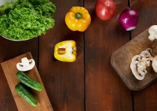 Surowe pieczarki, czerwona i żółta papryka, zielona sałata i fioletowa cebula