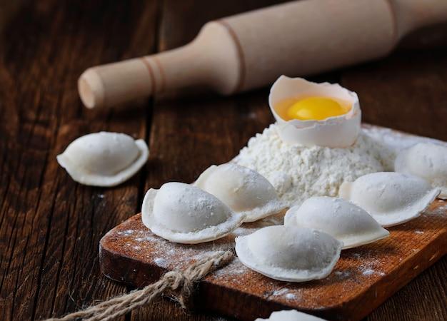 Surowe pierogi, mąka, jajko i wałek do ciasta