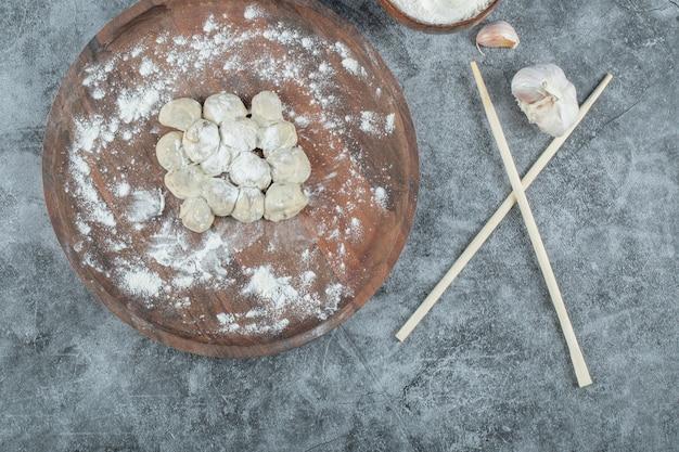 Surowe pierogi na drewnianym talerzu z pałeczkami.