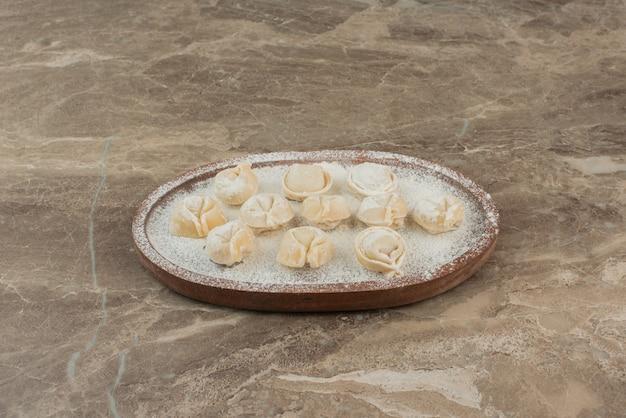 Surowe pierogi z mąką na drewnianym talerzu.