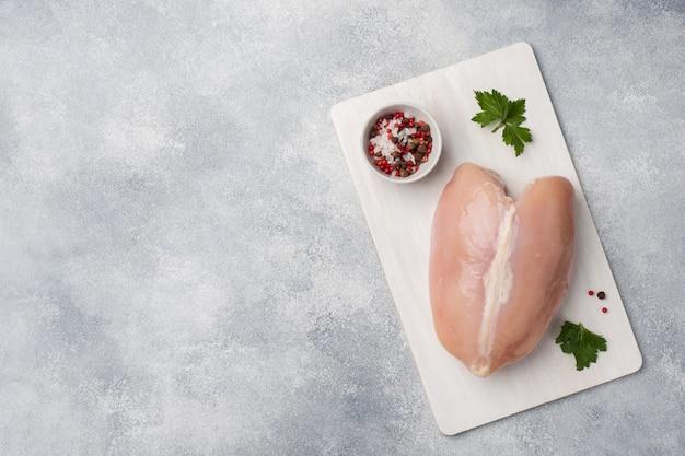 Surowe piersi z kurczaka i przyprawy na drewnianą deską do krojenia