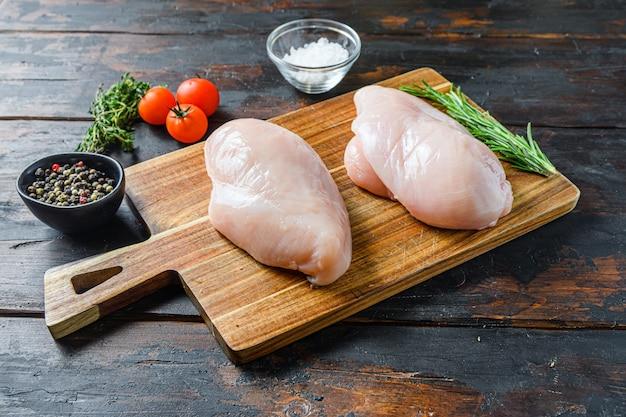 Surowe piersi z kurczaka i przyprawy na drewnianą deskę do krojenia na stary widok z boku ciemny stół.