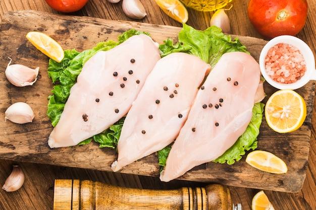 Surowe piersi z kurczaka i przyprawy na drewnianej desce do krojenia